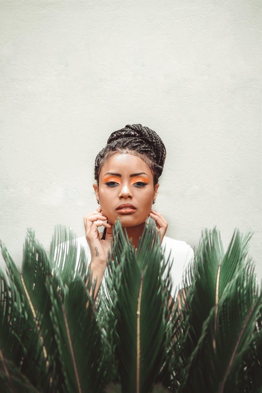 black woman standing near green plant
